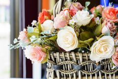 Beautiful flowers in basket on wooden table Stock Photo