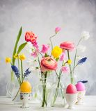 Festive Easter table. Beautiful flowers bouquets in glass vases on festive Easter table. Colored Easter eggs in egg cups stock image
