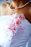 Beautiful flowers on the bride dress. Pink flowers on the beautiful bride dress. Bride with necklace Stock Photos