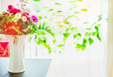 Beautiful flowers bunch in white vase on table at window background with green leaves Stock Image