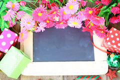 Beautiful flowers and gift box over chalk board Royalty Free Stock Photography