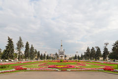 Beautiful flowers on the lawn and people walk. MOSCOW - September 2014: Palace with fountain, beautiful flowers on the lawn and people walking in the park at the Royalty Free Stock Photo