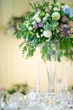 Beautiful flowers on the table event party or wedding reception. Luxurious flowers in a high vase on the table event party or wedding reception royalty free stock image