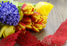 Beautiful flowers. Beautiful tulip and hyacinth flowers on wooden background. Knitted stripe Royalty Free Stock Image