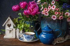 Cup of tea at summertime. Beautiful flowers in vase and cup of tea at wooden table, summer decor royalty free stock photos