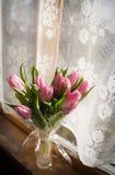Beautiful flowers in vase near window Royalty Free Stock Image