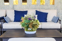 Beautiful flowers in vase on table in living room. Beautiful bouquets in a glass vase on the table and sofa in the living room royalty free stock photography