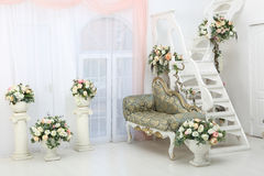 Beautiful flowers in vases on white stairs and sofa. Beautiful flowers in white vase on a ladder and elegant sofa Royalty Free Stock Images