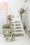 Beautiful flowers in vases on white stairs and sofa. Beautiful flowers in white vase on a ladder and elegant sofa Royalty Free Stock Photos