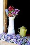 Beautiful flowers in white jug on wooden window royalty free stock photo