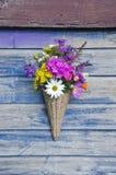 Beautiful  flowers in wicker basket on old wooden wall Stock Photo