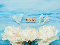 Beautiful flowers and words of love for Mother. Beautiful flowers and wooden letters of the alphabet with words of love for Mother on a blue background. Top view royalty free stock photography