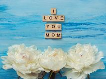 Beautiful flowers and words of love for Mother. Beautiful flowers and wooden letters of the alphabet with words of love for Mother on a blue background. Top view royalty free stock photo
