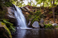 Beautiful Flowing Waterfall into a Tranquil and Peaceful Pool. Water flows peacefully over the steep cliff of Hungarian Falls waterfall in Michigan's Upper Royalty Free Stock Photo