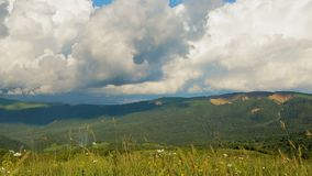 Beautiful fluffy clouds running on blue sky over high hill mountains, time-lapse stock footage
