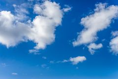 Fluffy white clouds against a bright, colorful blue sky stock images