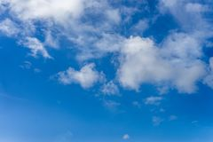 Fluffy white clouds against a bright, colorful blue sky royalty free stock photography