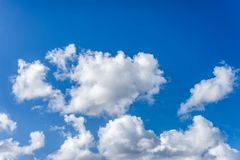 Fluffy white clouds against a bright, colorful blue sky. Beautiful fluffy white clouds of varying thickness rolling through a bright, colorful blue daytime sky stock photography