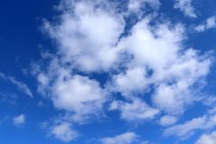 Beautiful fluffy white cumulus and cirrus clouds on a deep blue sky. Seen in nothern germany royalty free stock image
