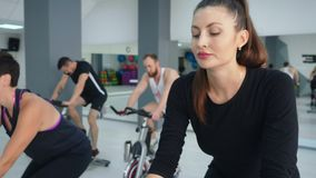 Beautiful focused woman cycling on spin bike at cycling class stock video footage