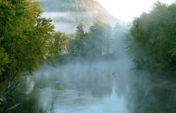 Beautiful Fog covered Swift river with Distant Mountain Royalty Free Stock Image