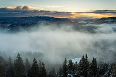 Beautiful fog over forest in mountin with sunrise in background.  Stock Image