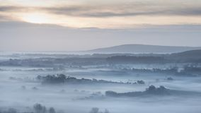 Stunning foggy English rural landscape at sunrise in Winter with Royalty Free Stock Photos