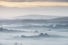 Stunning foggy English rural landscape at sunrise in Winter with. Beautiful foggy English countryside landscape at sunrise in Winter with layers rolling through Royalty Free Stock Photography