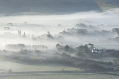 Stunning foggy English rural landscape at sunrise in Winter with. Beautiful foggy English countryside landscape at sunrise in Winter with layers rolling through Royalty Free Stock Image