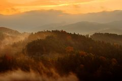 Beautiful foggy landscape. Cold misty foggy morning with twilight sunrise in a fall valley of Bohemian Switzerland park stock photography