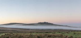 Beautiful foggy sunrise landscape over the tors in Dartmoor reve. Stunning foggy sunrise landscape over the tors in Dartmoor revealing peaks through the mist royalty free stock images