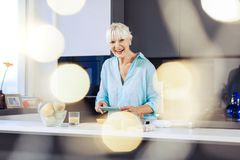 Cheerful happy aged woman taking photos in the kitchen. Beautiful food. Cheerful aged woman smiling while taking photos of food in the kitchen royalty free stock photos