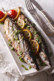 Beautiful food: grilled fish with lemon on a plate close-up. ver Stock Images