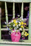 Beautiful forest  flowers in pink vase on a green wooden chair Stock Image