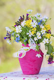 Beautiful forest flowers in pink vase with ribbon stock image