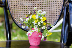 Beautiful forest  flowers in pink vase with ribbon on a wooden chair Royalty Free Stock Photos