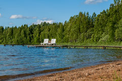 Beautiful forest lake with a beach place for a quiet relaxing holiday on a wooden pier. Sunny day stock image
