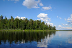 Beautiful forest at the lake's edge. The beautiful picture of Karelian forest at the edge of a lake, and some huge boulder in this lake stock photos