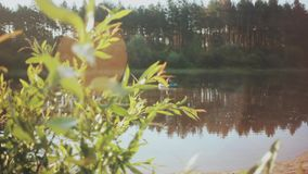 Beautiful forest landscape of the lake and plants. Two man fishing in the rubber boat, resting together on the nature. stock video footage