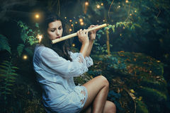 Beautiful forest nymph playing  flute with fairies. Romance and fantasy Royalty Free Stock Photography