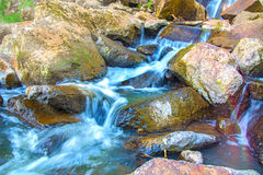 Beautiful forest waterfall. on the stony slope runs stormy forest waterfall. In the Sun Stock Photo