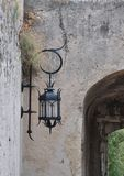 Beautiful forged lantern on the wall of the Monaco castle. Wrought iron lantern on the grey stone wall  of the Monaco castle Stock Photography