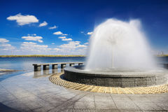 Beautiful fountain against the blue sky with clouds IX Royalty Free Stock Image
