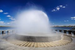 Beautiful fountain against the blue sky with clouds VII Stock Photos