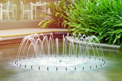 Beautiful fountain on the background of tropical plants. located in a hotel in the subtropics. landscape design royalty free stock photography