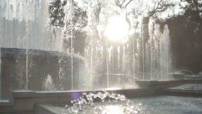 Beautiful fountain in city park. The sun illuminates splashes of water. Shining splash of water stock footage