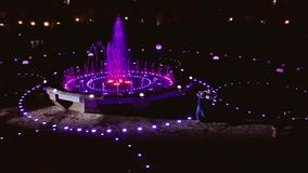 Beautiful fountain at night and dancing couple nearby. stock video footage