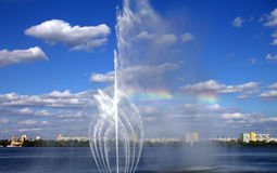 Beautiful fountain with a rainbow on the river. Stock Photo
