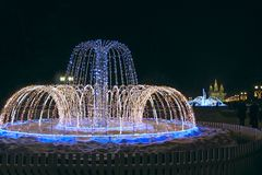 Beautiful fountains in city park. Colorful New Year garlands