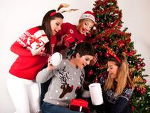Four girls are surprised with Christmas presents boxes royalty free stock images